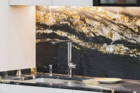 Beautiful modern kitchen design, kitchen faucet, black and gold stone marble countertop kitchen.