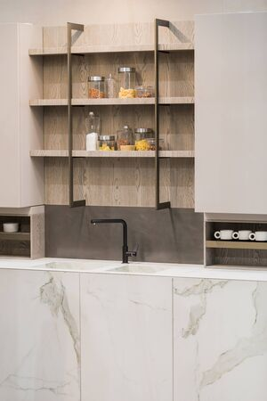Modern kitchen white marble texture, black faucet and marble sink, hanging wooden sideboard shelves.