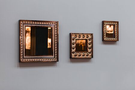 Three mirror frames on grey wall. Triptych scenery frames mirrored golden copper color. 免版税图像