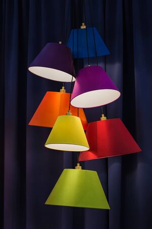 Hanging color lampshades on dark background. Composition of multi-colored chandeliers in interior design.