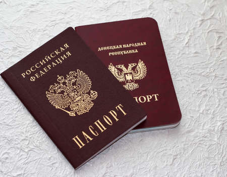 Passport of the Russian Federation on a light background. The inscription in Russian: Russian Federation, passport. Passport of the Donetsk people's Republic on a white crumpled background. The inscription in Russian: Donetsk people's Republic, passport.