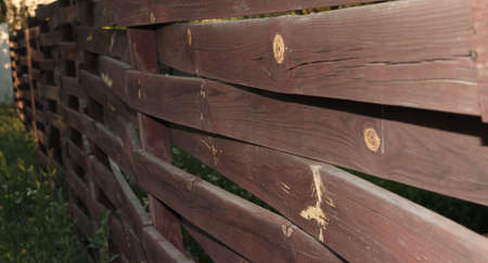 Brown wooden old fence. The wooden planks are intertwined.