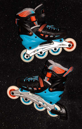 Roller skates on a black background. Rollers are black and blue with orange.