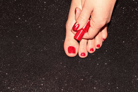 Red pedicure and manicure. A woman's leg and hand with a jar of nail Polish on a black background