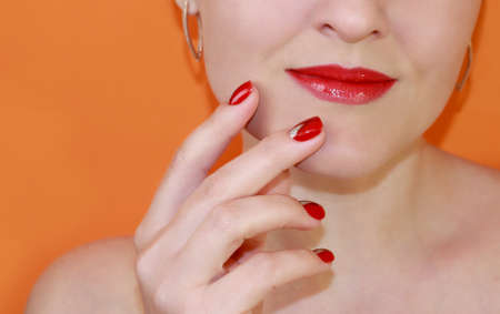Lips with red lipstick and red manicure on an orange background. Classic lipstick color. Byuti background.