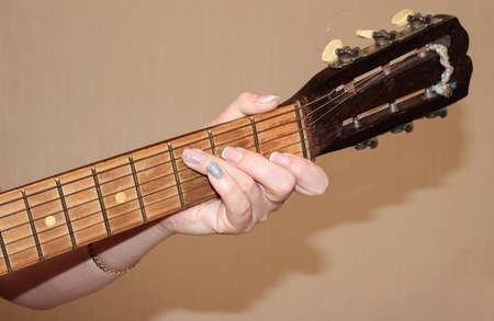 A woman's hand with a manicure holds a chord on a guitar. The girl plays the guitar. Fingerboard and frets. Stock Photo