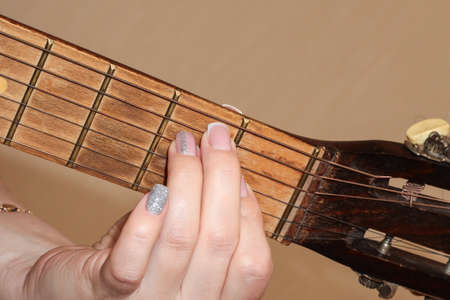 A woman's hand with a manicure holds a chord on a guitar. The girl plays the guitar. Fingerboard and frets.