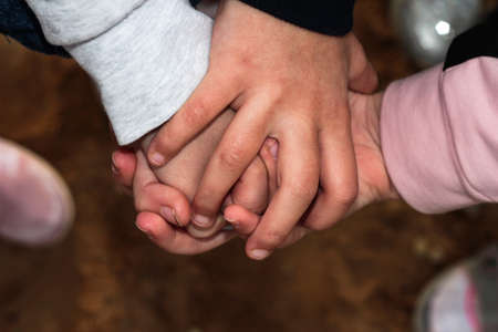 Crossed children's hands. Lots of fingers. Symbol of friendship. One for all and all for one. Stock Photo