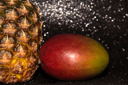 Pineapple with mango on a black shiny background. Half a pineapple and a whole mango in the skin.