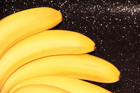 Bananas on a black background with bokeh and glitter. A fan of banana bunches.