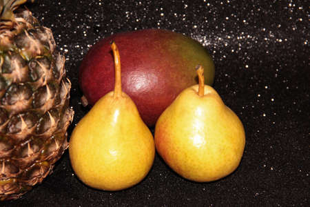 Pears with pineapple and mango on a black background. Zdjęcie Seryjne