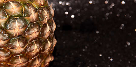 Part of a pineapple on a black shiny background