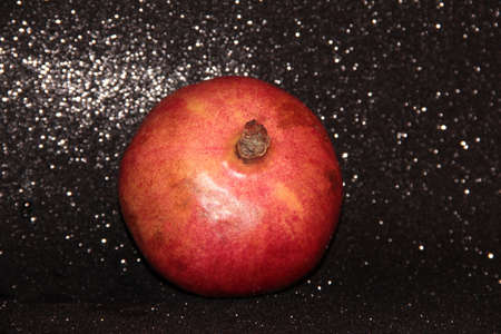 Pomegranate fruit on a black shiny background. One grenade.