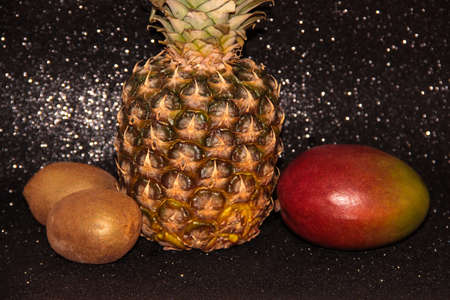 Pineapple with kiwi and mango on a black shiny background