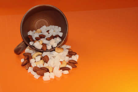 Cashew nuts, almonds and coconut in a mug on an orange background