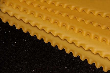 Pasta on a black shiny background. Lasagna sheets on a dark background. Food frame. Stock fotó