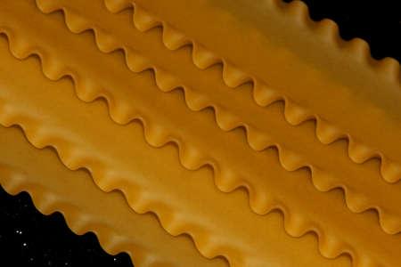 Pasta on a black shiny background. Lasagna sheets on a dark background. Food frame.
