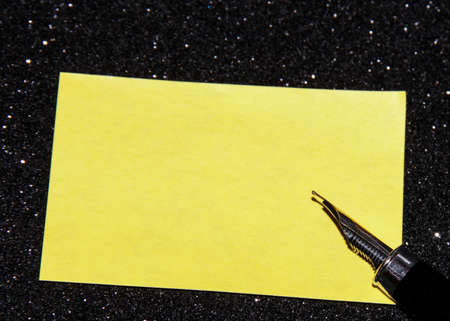 Fountain pen on a black background with a yellow sheet for text.