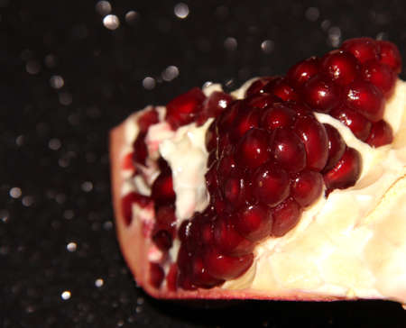 Pomegranate slice with berries on a black background. Brilliant background with berries.