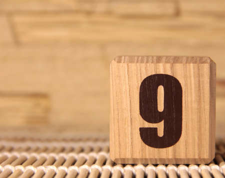 A wooden cube with the number nine on a beige background. Stock Photo