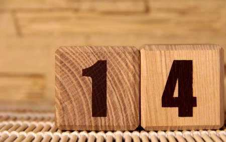 The number fourteen on a wooden cube on a beige background. Cube on a bamboo Mat.