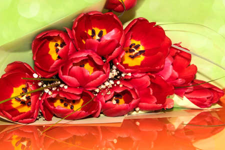 Red open tulips on the orange table. Gorgeous spring flowers. Bouquet for the woman you love