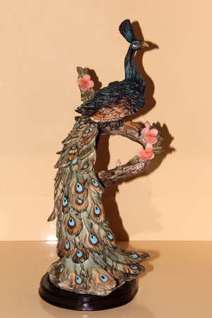 Statuette of a peacock sitting on a stump