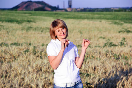 Blonde in jeans in a field with wheat Stock fotó