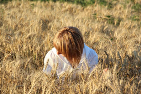Portrait of a girl sitting in spikelets of wheat