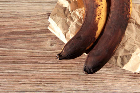 Spoiled bananas on a wooden background. Fruit