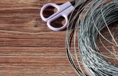Wire on a wooden background with purple scissors. Archivio Fotografico