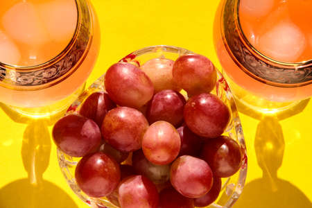 Grapes in a crystal bowl with an icy drink on a bright background.