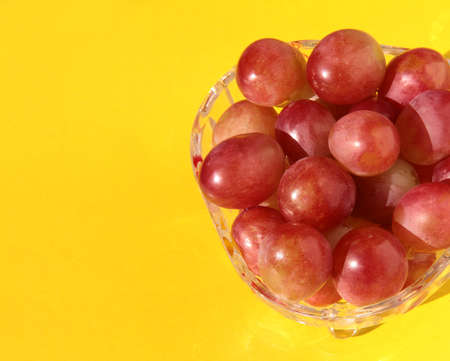 Grapes in a crystal vase on a bright yellow background.