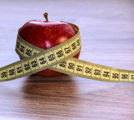 A red Apple is measured by a meter. Slimness and diet.