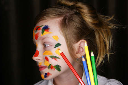 A girl stained with paint holds colored pencils.