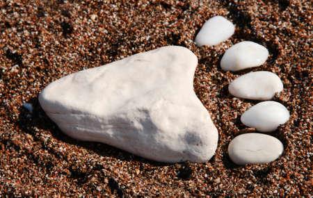Leg made of sea stones. White sea pebbles. Sea background.