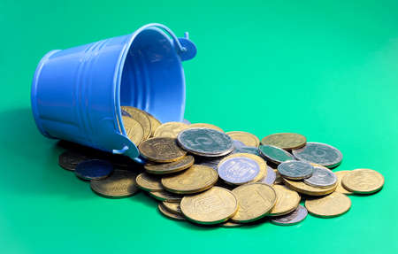 Coins spilled out of the bucket. Ukrainian coins on a green background.