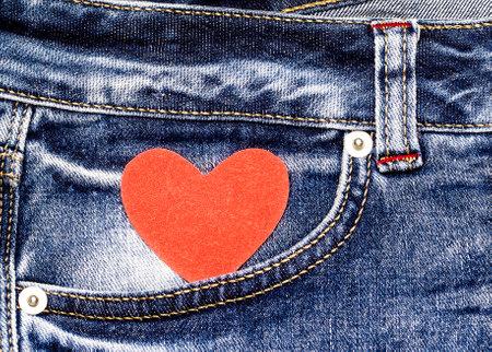 Red heart in jeans pocket. Love symbol. Valentine's card.