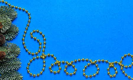 Blue background with gold beads and fir branches.