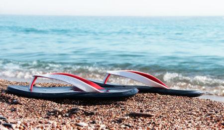 Men's sandals on the sea sand. Marine background. Standard-Bild