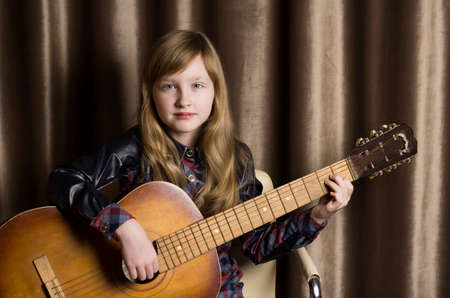 Little girl with a guitar on a brown background.