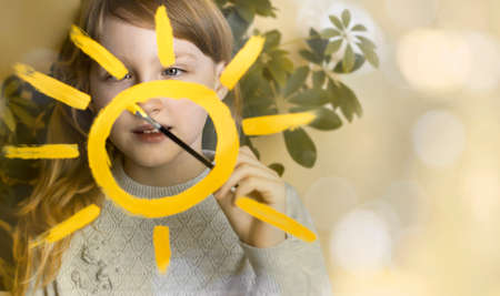 The child draws the sun on the window. A game. Drawing. Banque d'images