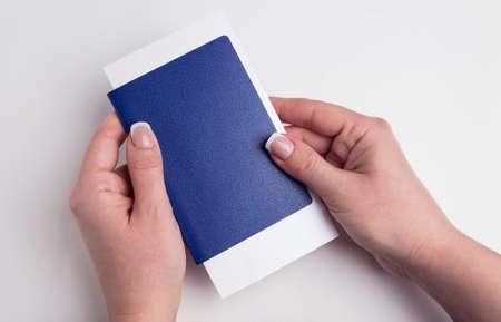 Blue passport in female hands. Human immunity passport on a white background.