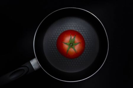 Tomato in the center of a saucepan, all on black background