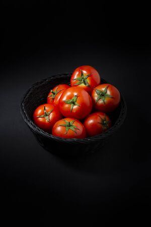 Tomatoes in black basket, all on black background