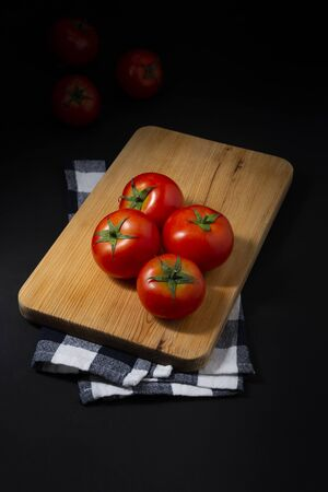 Tomatoes on chopping board, all on black background