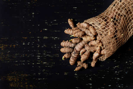 Jute sack with turmeric roots, all on a dark colored wooden background - turmeric