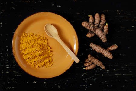 Orange bowl with turmeric powder and a wooden spoon, next to it, turmeric roots, all on a dark colored wooden background - turmeric