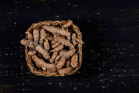 Jute basket with turmeric roots, all on a dark colored wooden background - turmeric