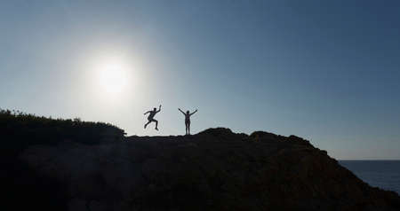 Silhouette of two people jumping happy, on top of a mountain, at sunset.